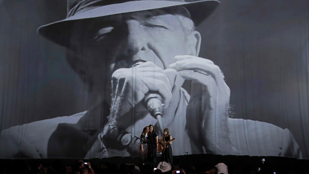 Feist on stage in front of a Leonard Cohen Photo